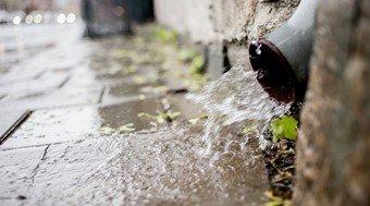 Vann fosser ut av en takrenne ved en bilvei